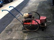 在小卵石地板上的老柴油割草机 免版税库存图片