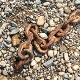 在小卵石海滩的生锈的链子  免版税库存图片