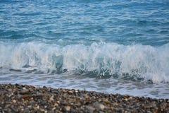 在小卵石的海波浪 库存照片