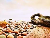 在小卵石的Bizzare岩石靠岸,上面剧烈的天空 石近海 库存图片