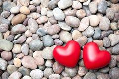 在小卵石石头的两红色心脏 免版税库存图片