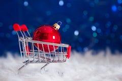 在小型超市台车的红色圣诞节球在蓝色bokeh ba 免版税库存图片