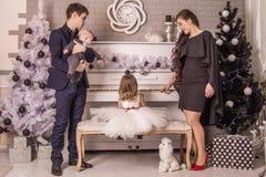 在小女儿附近的家庭在圣诞节的钢琴的 免版税库存照片
