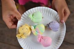 在小女孩手盘子的五颜六色的冰淇凌  库存照片