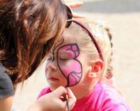 在小女孩的面孔的艺术家油漆 免版税库存图片