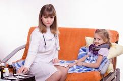 在小女孩附近的医生采取从桌的医学 库存图片