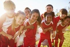 在小学扛在肩上的体育队的孩子户外 免版税库存图片
