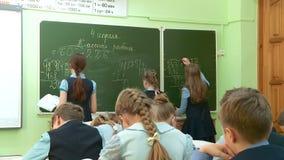 在小学生的算术教训解决问题在黑板和在他们的书桌 股票录像