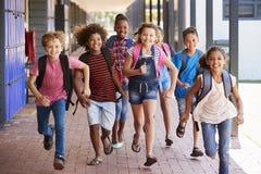 在小学走廊,正面图教育跑的孩子 免版税图库摄影