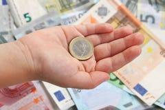 在小孩子的手上的一枚欧洲硬币在欧洲钞票背景  免版税库存照片