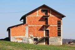在小小山的边的未完成的大红砖郊区家庭房子围拢与未割减的草 免版税图库摄影