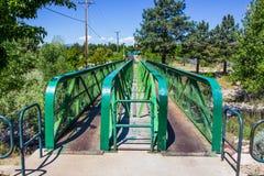 在小小河的绿色走的桥梁 免版税库存图片