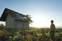 在小山上面的年轻人伸手可及的距离然后享受从上面的日出 图库摄影