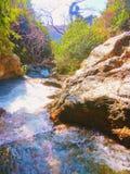 在小山下的小河 免版税库存照片