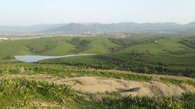 在小山之间的美丽的湖在春天 免版税库存图片