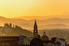 在小山和城市的日落 图库摄影