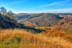 在小山和未开发的地区有树的和草的美好的五颜六色的秋天风景的看法在乡下 免版税图库摄影