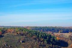 在小山和未开发的地区有树的和草的美好的五颜六色的秋天风景的看法在乡下 库存图片