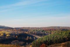 在小山和未开发的地区有树的和草的美好的五颜六色的秋天风景的看法在乡下 免版税库存照片