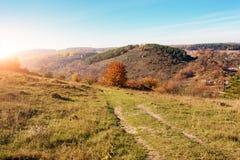 在小山和未开发的地区的美好的五颜六色的秋天风景的看法与树的在乡下 库存照片