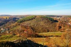 在小山和未开发的地区的美好的五颜六色的秋天风景的看法与树的在乡下 库存图片