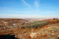 在小山和未开发的地区的美好的五颜六色的秋天风景的看法与树的在乡下 图库摄影