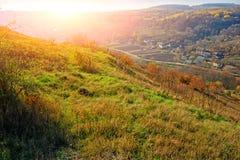 在小山和未开发的地区的美好的五颜六色的秋天风景的看法与树的在乡下 免版税库存照片