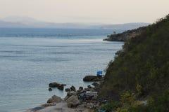 在小山和海洋之间的小屋 免版税库存照片
