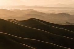 在小山和谷的日落 免版税库存照片
