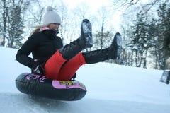 在小山明亮和快乐的冬天场面下的一年轻女人Sledging 库存照片