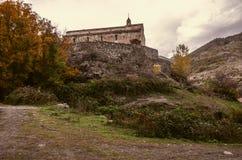 在小山的Ðœedieval monasteryancientÂ石墙的在秋天阴云密布天 免版税图库摄影