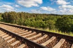 在小山的一条铁路与背景的绿色森林 库存图片