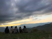 在小山的上面的愉快的家庭就座与狗的 免版税库存照片