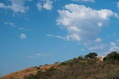 在小山的上面的暗藏的房子反对深蓝天的 免版税库存照片