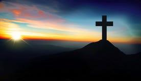 在小山的基督徒十字架在日落 免版税库存图片