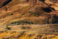 在小山的少女峰铁路火车在克莱茵沙伊德格驻地,少女峰地区附近 免版税库存图片