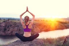 在小山的少妇实践的瑜伽在日落 库存照片