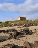 在小山的教会在海滩附近 库存图片