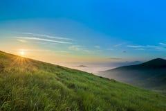 在小山的日出在与绿草和蓝天wi的山 免版税库存照片
