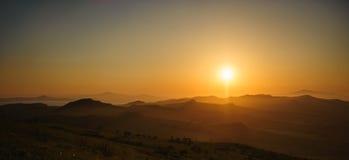 在小山的日落 免版税库存照片