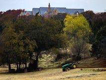 在小山的树几乎掩藏的宏伟的房子与国家牧场地和篱芭和拖拉机在前景 库存照片
