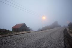 在小山的美丽如画的房子废墟在雾在早晨 街道在离开的村庄 免版税库存照片