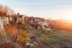 在小山的美好的五颜六色的秋天风景的看法与树、岩石和未开发的地区的在乡下 库存图片
