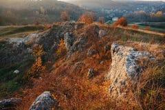 在小山的美好的五颜六色的秋天风景的看法与树、岩石和未开发的地区的在乡下 免版税库存照片