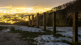 在小山的雪在城市上 免版税库存图片