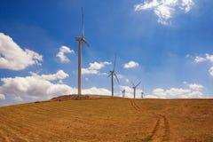 在小山的风车反对与白色云彩的蓝天 黑山, Krnovo在Niksic镇附近的风公园 免版税库存照片