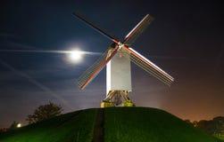 在小山的风车在晚上在布鲁日,比利时 免版税库存照片