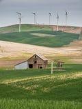 在小山的风轮机冠上与麦田和谷仓 库存照片
