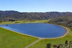 在小山设置的清楚的蓝色水库在北岛,新西兰 免版税库存照片