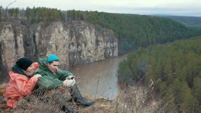 在小山边缘的年轻夫妇远足者休闲在山河 股票视频